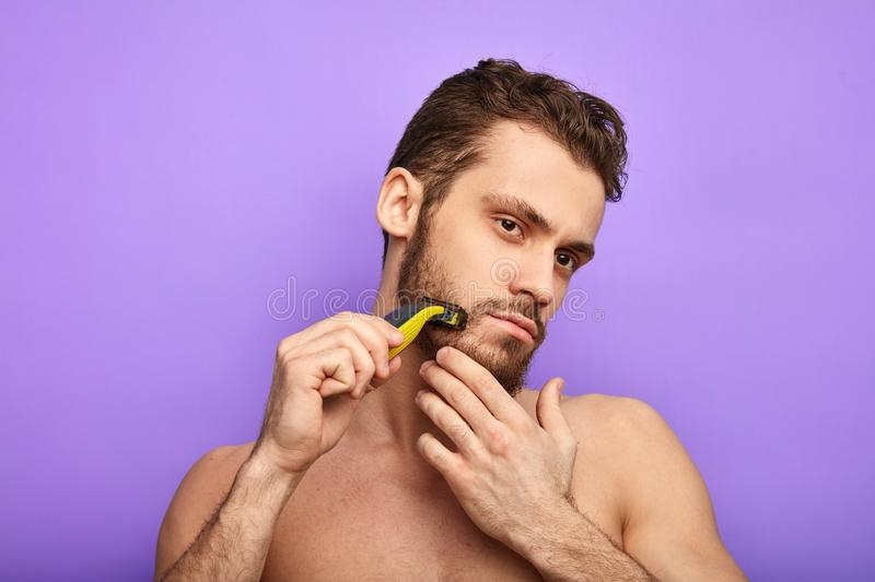 Serious man shaving without foam stock images