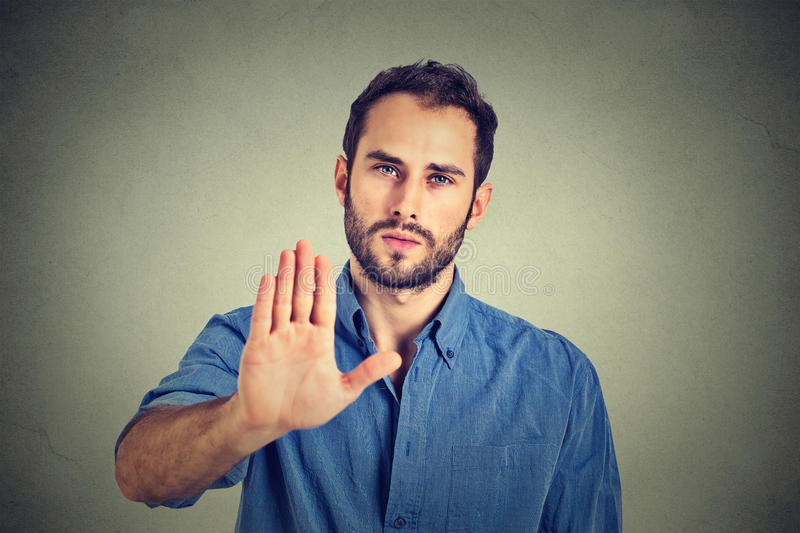 Serious man showing stop gesture isolated on gray wall background royalty free stock images