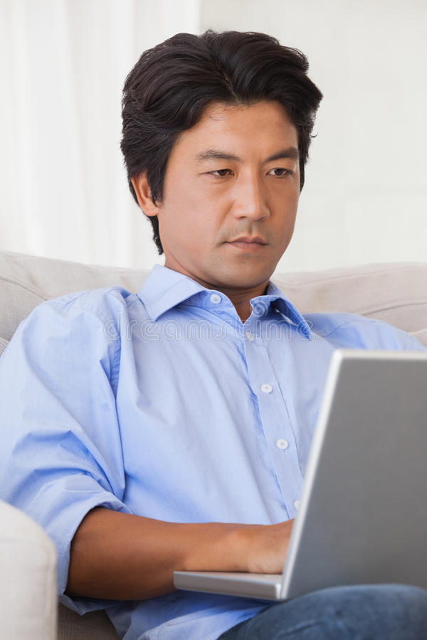 Free Serious Man Sitting On Couch Using Laptop Royalty Free Stock Photo - 39429585
