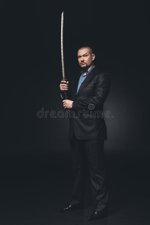 serious man in suit with japanese katana sword stock photo