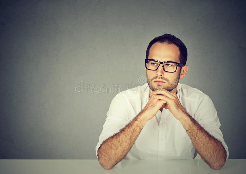 Serious man at table thinking stock photo