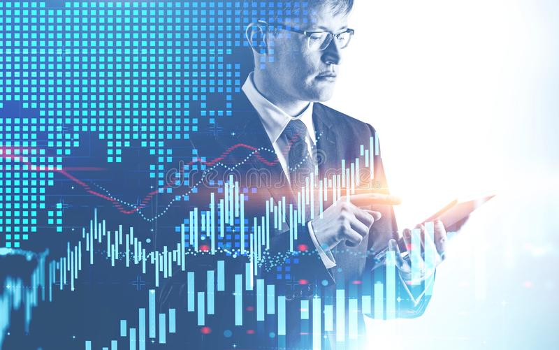 Serious man with tablet, forex graph. Serious young caucasian businessman in glasses working with tablet computer with double exposure of forex graphs. Concept stock photography