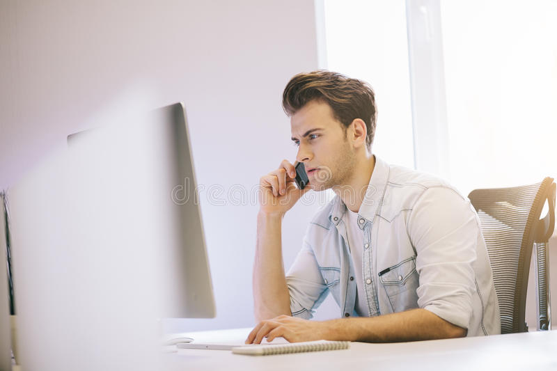 Serious man talking on mobile phone while using laptop computer at desk in study. Looking of the working man in the office. The guy makes a business call royalty free stock image