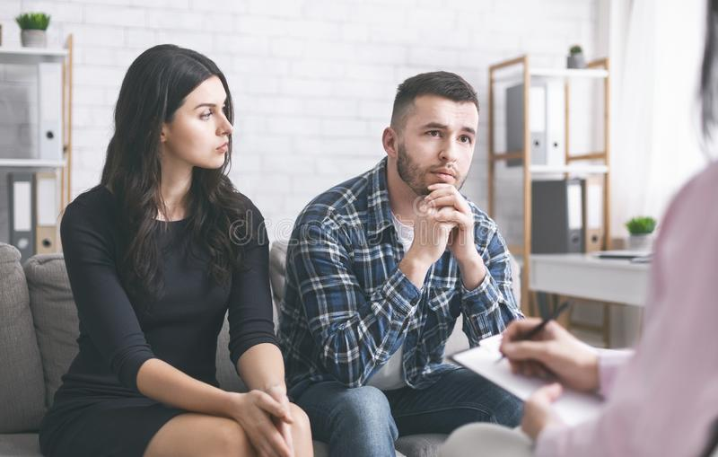 Serious man talking to psychiatrist during marital therapy session stock photos