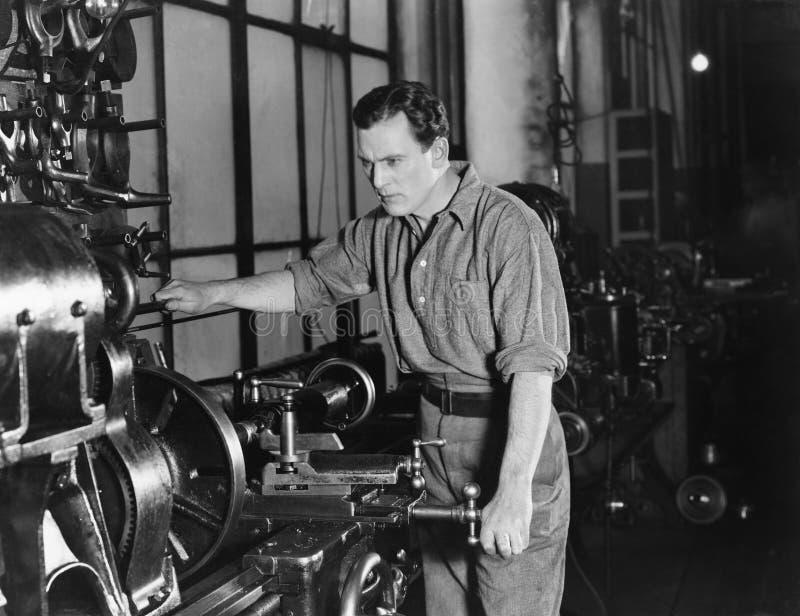 Serious man using large machine stock image