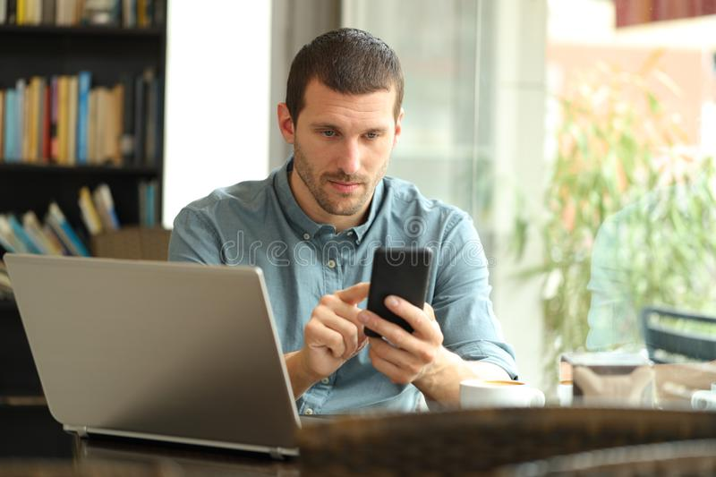 Serious man using smart phone and laptop in a bar. Serious man using smart phone and laptop sitting in a coffee shop royalty free stock photography