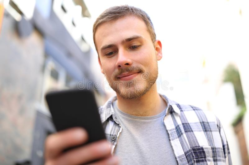 Serious man walks using smart phone in the street stock photo