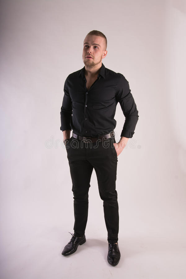 Serious man Wearing black shirt and black pants standing and looking forward. Full length Studio portrait stock photos