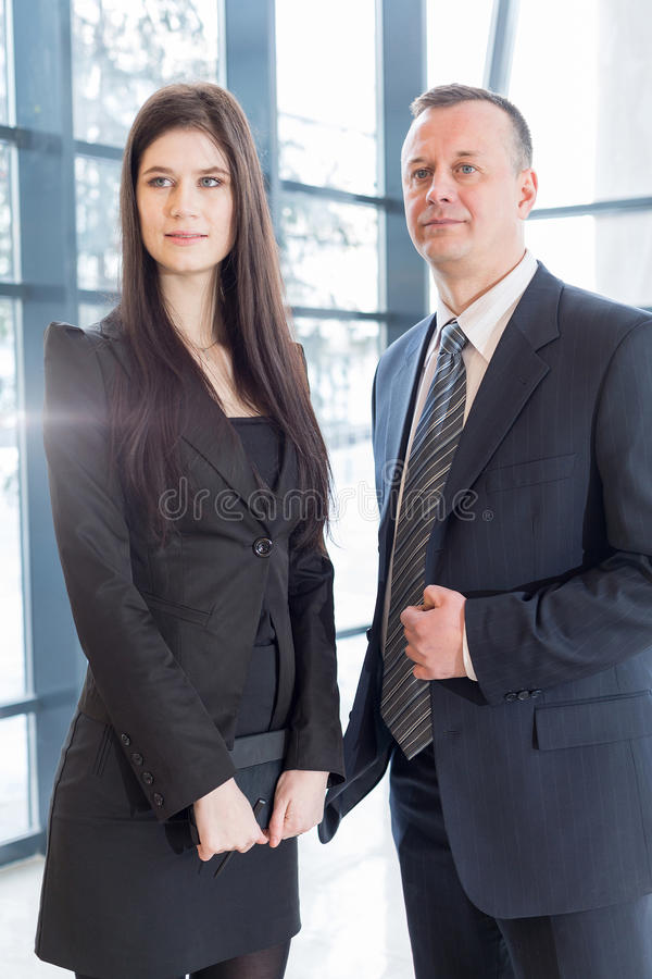 Serious man and woman in business suits stand stock photos