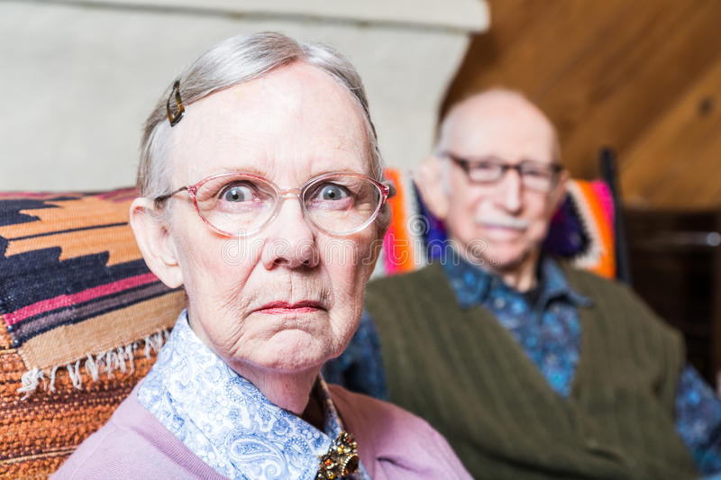 Serious Man and Woman Indoors. Old couple seating in livingroom women scowling royalty free stock image