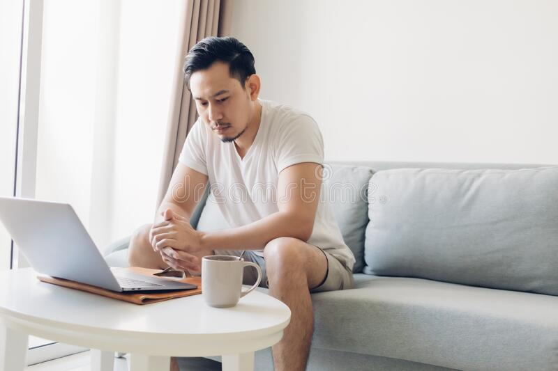 Serious man is working on his laptop in the living room. royalty free stock photo