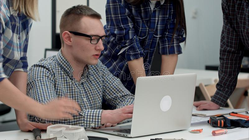 Serious manager in glasses looking at computer and talking to his team royalty free stock photos