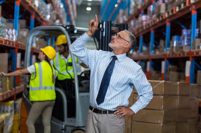 Serious manager pointing shelves with hand on hips royalty free stock photos