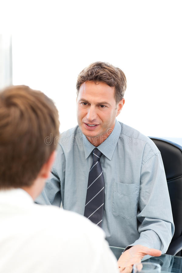 Serious manager talking with an employee. During an interview at the office stock photos