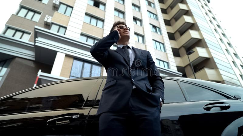 Serious manager talking on phone, standing by car, waiting for investor, stress. Stock photo stock images