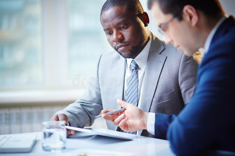 Serious managers. Male partners discussing importrant things royalty free stock photos