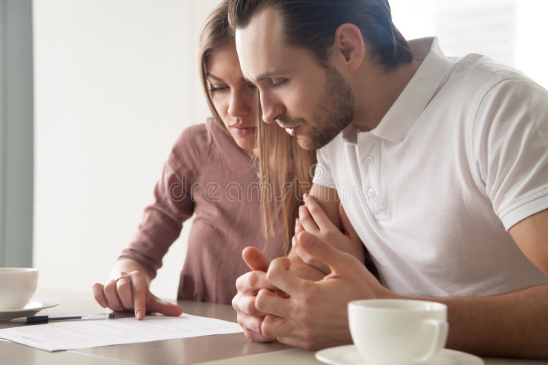 Serious married couple with papers, considering loan offer, calc stock photography