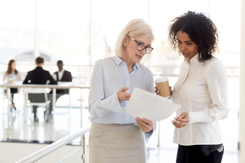 Serious mature businesswoman show document to African American colleague royalty free stock photography