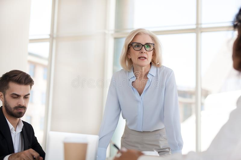 Serious mature businesswoman talk having discussion during brief royalty free stock photography