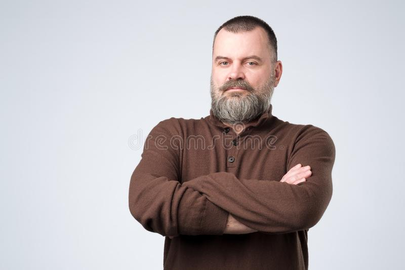 Serious mature european man standing with arms folded royalty free stock photography