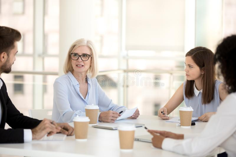 Serious mature executive speaking at office briefing to employee stock photos