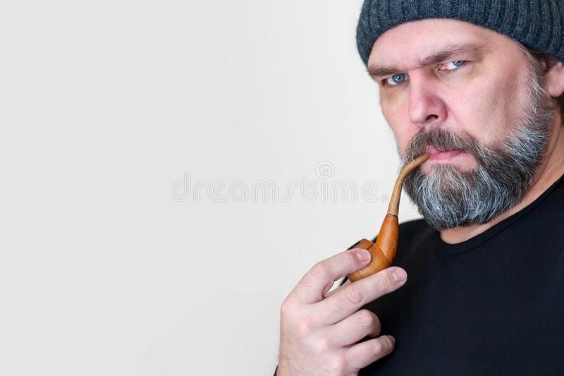 Serious Mature middle-aged man with a beard, Smoking a pipe, looking at the camera. A middle-aged man, like a seasoned sailor, smokes a pipe. With copy space royalty free stock photo