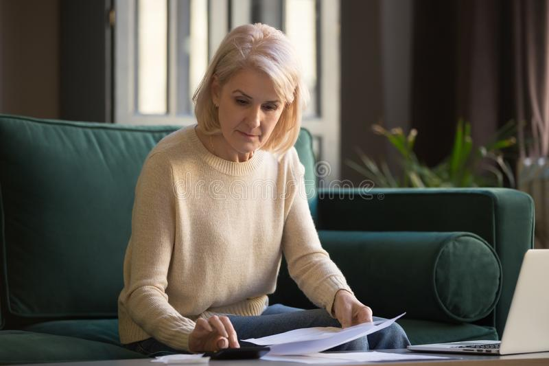 Serious mature woman holding bills doing paperwork using calculator royalty free stock photo