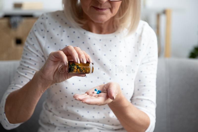 Serious mature woman taking out pills from bottle close up royalty free stock photo