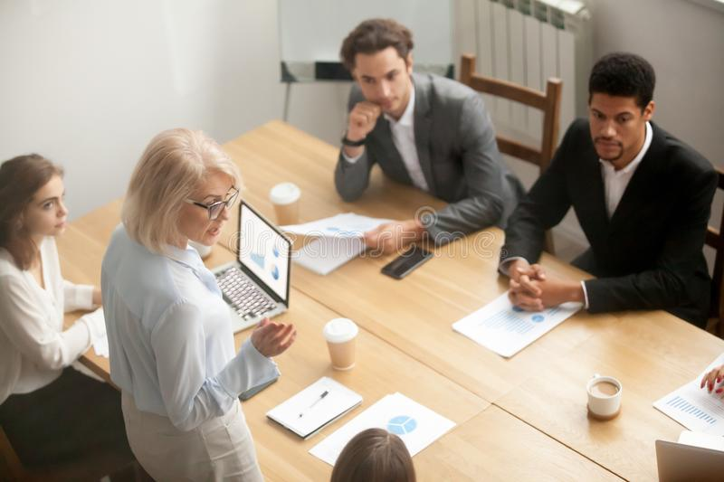 Serious mature woman team leader speaking at diverse team meetin stock photography