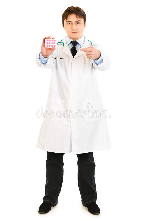 Serious medical doctor pointing at pack of pills royalty free stock images