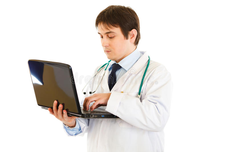 Serious medical doctor working on laptop stock image