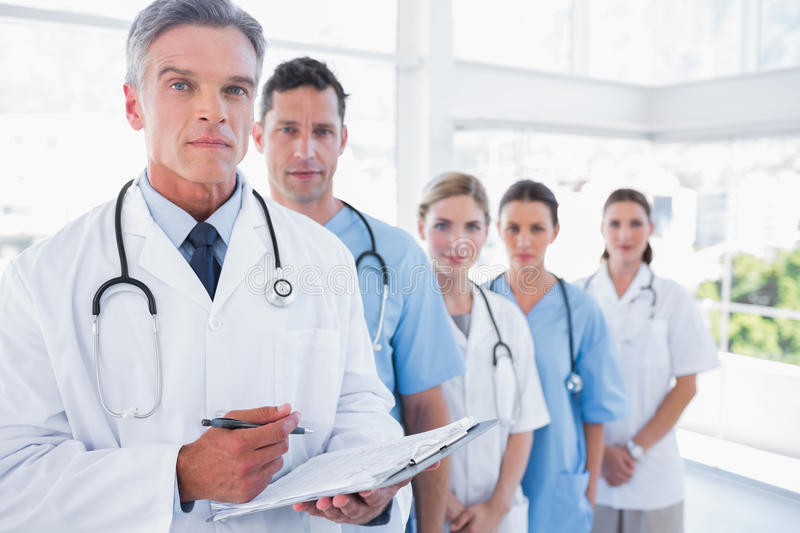 Serious medical team in row stock photo