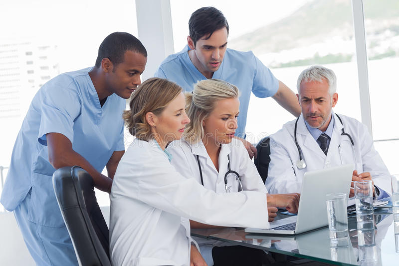 Serious medical team using a laptop royalty free stock photo