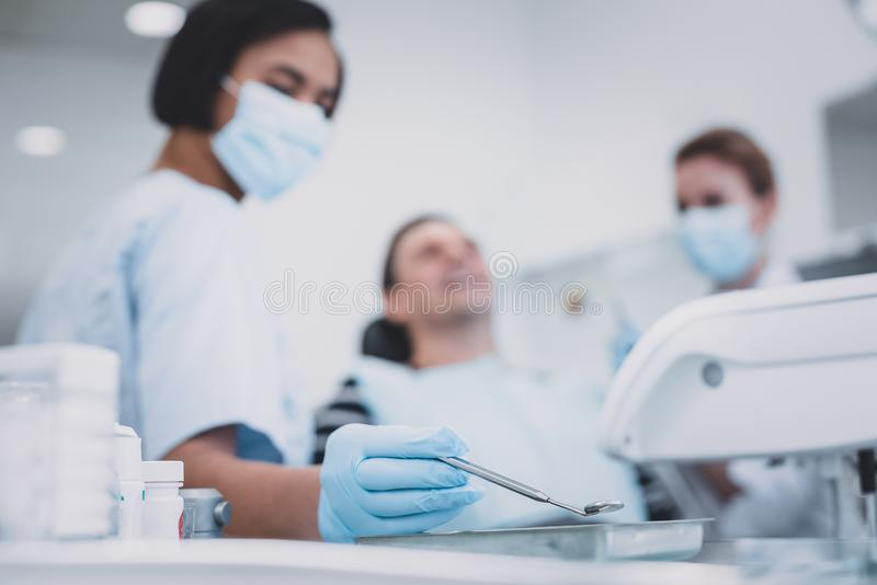 Serious medical worker going to treat her patient royalty free stock photos