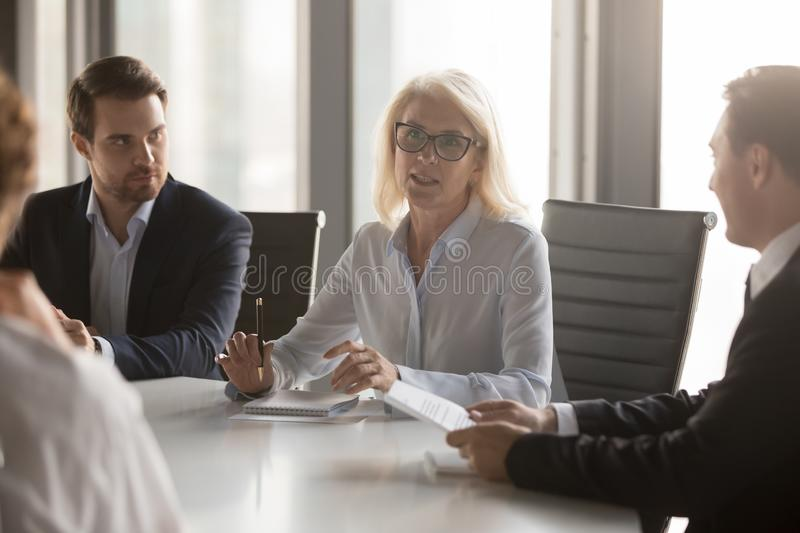 Serious middle aged businesswoman talks at group board executive meeting. Confident mature old female leader speaking discussing work offers solution royalty free stock photos