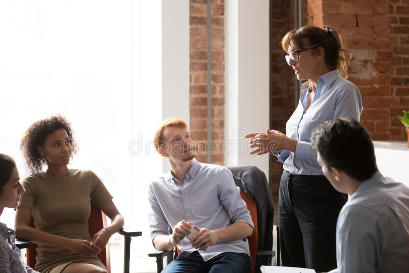 Serious coach leader speaking teaching diverse staff at group meeting stock photo