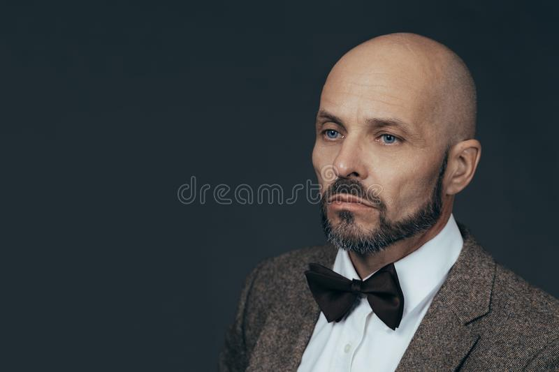 Serious middle aged man with a deadpan face expression dressed in casual posing on a dark gray background stock image