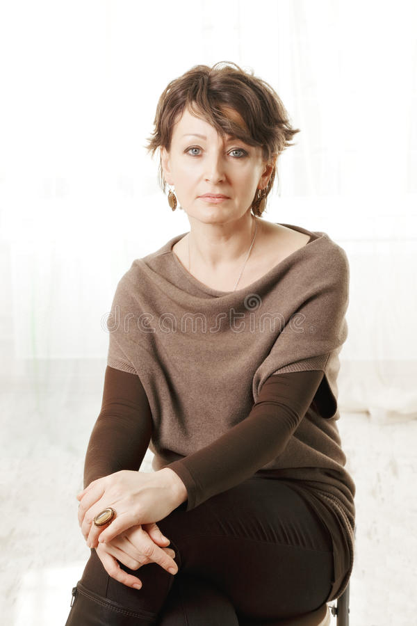 Serious middle aged woman in brown sweater royalty free stock images