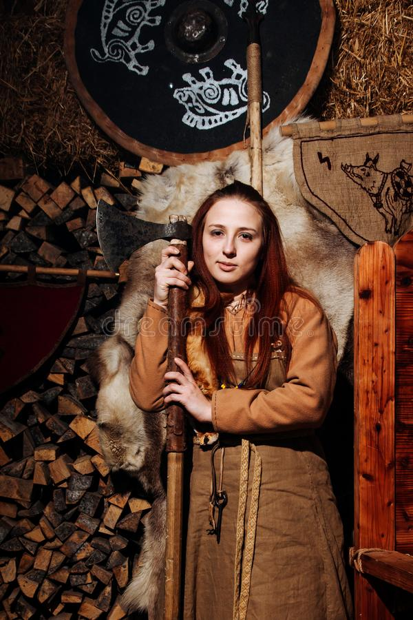 Viking sword handles sword rack reenactment forge smith warrior weapon outfit ax shield skin hearth one woman girl portraite. Serious militant Viking girl stands royalty free stock photography