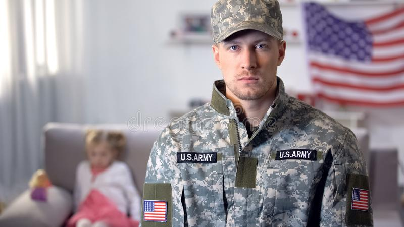 Serious military man looking at camera, little daughter on background, support. Serious military men looking at camera, little daughter on background, support royalty free stock images
