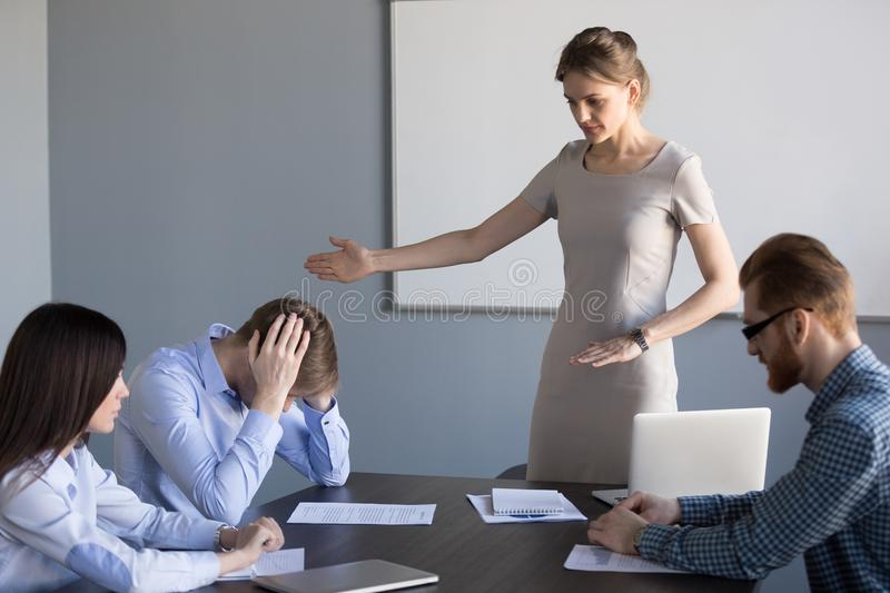 Serious businesswoman ask failed employee to leave meeting. Serious millennial businesswoman fire failed unprofessional employee, ask him to leave team meeting royalty free stock photos