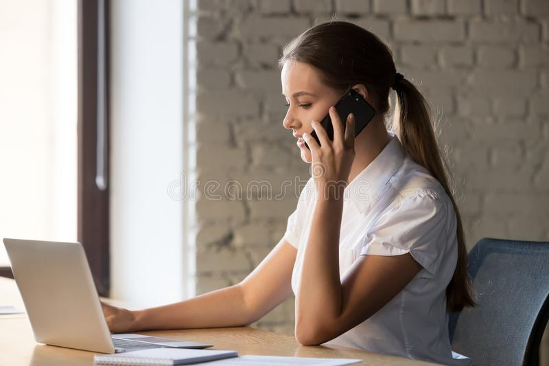 Focused female employee using laptop and talking on mobile royalty free stock photography