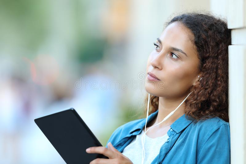 Serious mixed race woman thinking listening to music royalty free stock photos