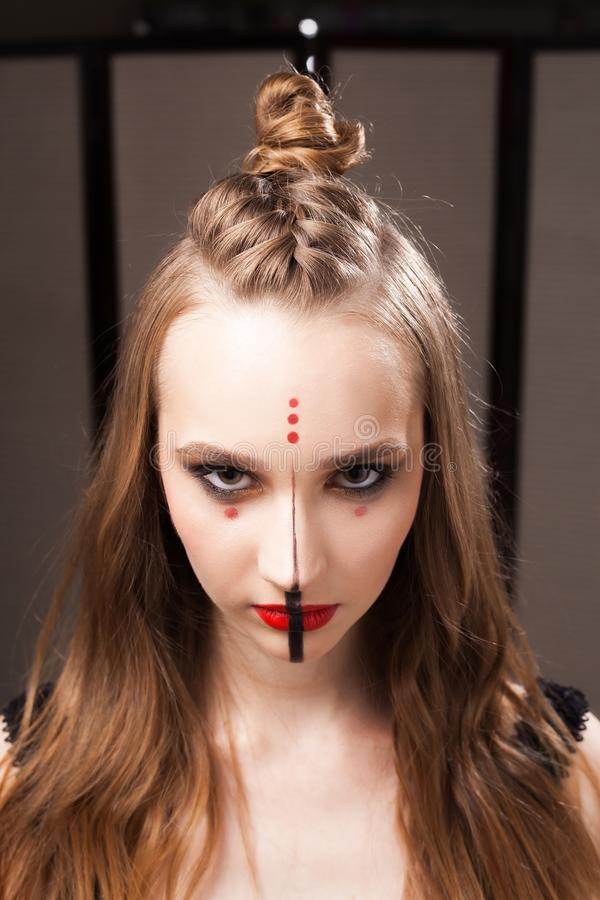Serious model with unusual makeup and coiffure. Beautiful young serious girl model with professional unusual makeup and a coiffure with topknot and braid made by stock images