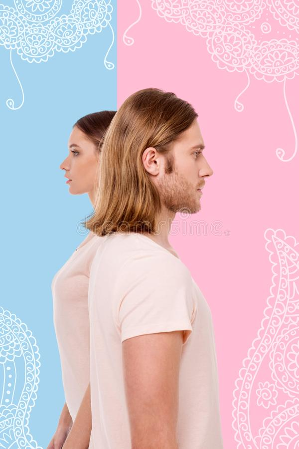 Serious models standing with their backs straight while posing. Professional models. Skilled experienced models standing back to back and looking calm while royalty free stock photo