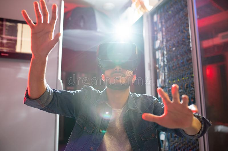 IT specialist using virtual reality goggles in server room stock image