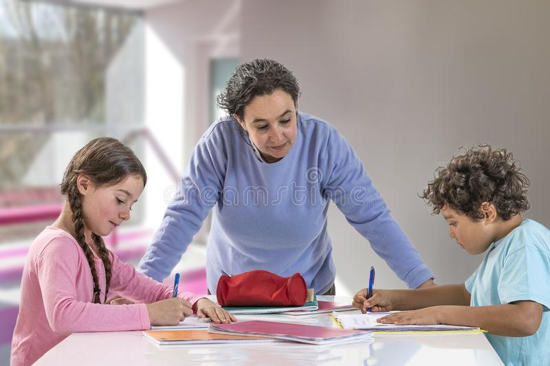 Serious mother helping their child to do homework at home royalty free stock images