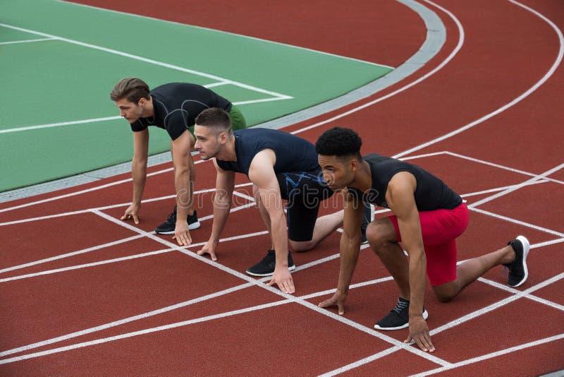 Serious multiethnic athlete group ready to run stock photo
