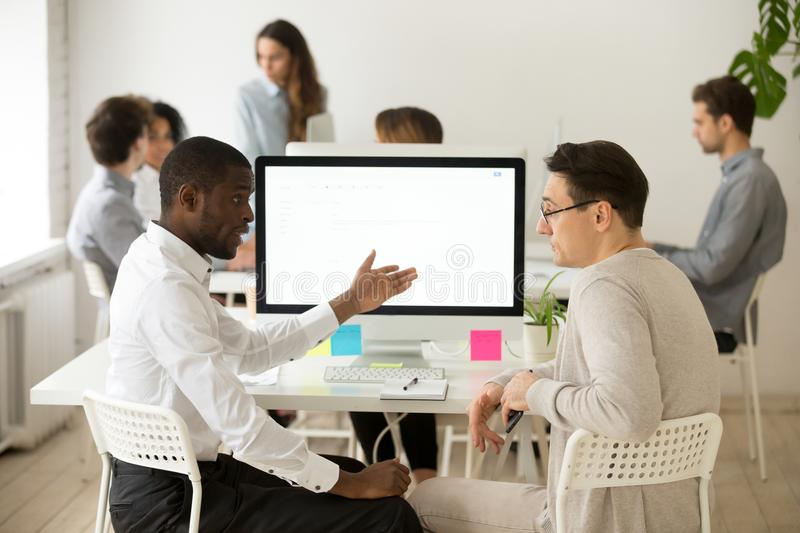 Serious multiracial colleagues having discussion brainstorming p. Serious multiracial colleagues talking discussing project together in office, african manager royalty free stock photo