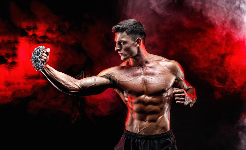 Serious muscular fighter doing the punch with the chains braided over his fist. Serious muscular fighter doing the punch with the chains braided over his fist royalty free stock photo